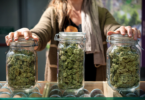 woman with jars of cannabis